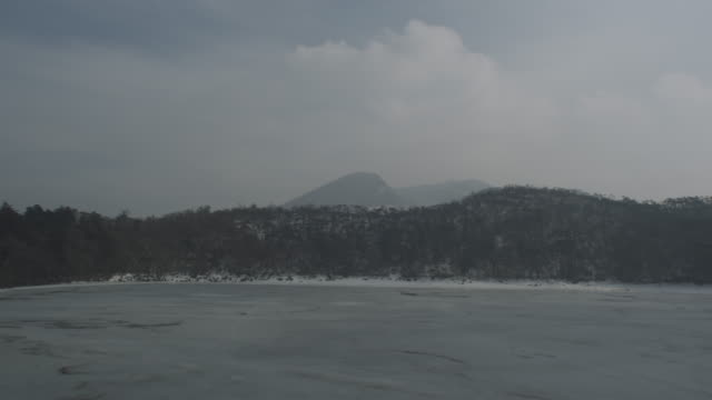 frozen lake with volcano and forest in background, kirishima volcano, japan, 2011 - frozen stock videos and b-roll footage