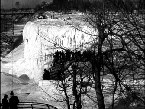 stockvideo's en b-roll-footage met frozen niagara falls with tourists on top / man running on ice niagara falls freezes over on february 26 1934 in niagara new york - niagara falls city staat new york