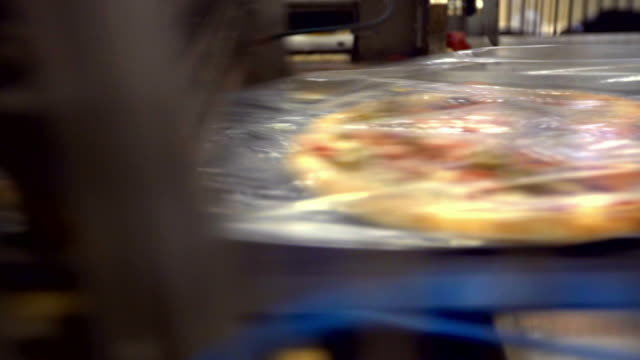frozen pizzas in cellophane on assembly line - cibi surgelati video stock e b–roll