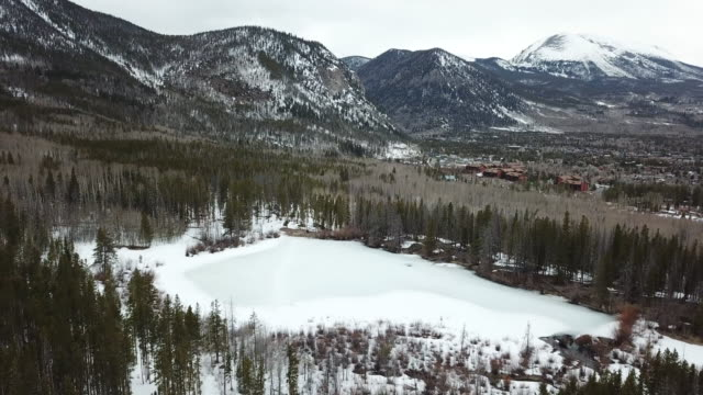 frozen pond in forest clearing, mountains in background, aerial in - pond stock videos & royalty-free footage
