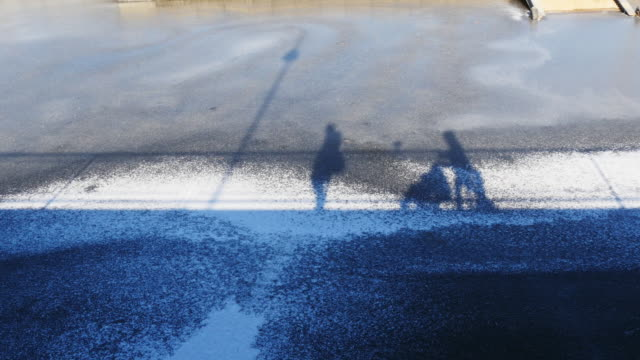 frozen pond with shadows of two persons with a stroller passing by on bridge - vieux montréal stock-videos und b-roll-filmmaterial