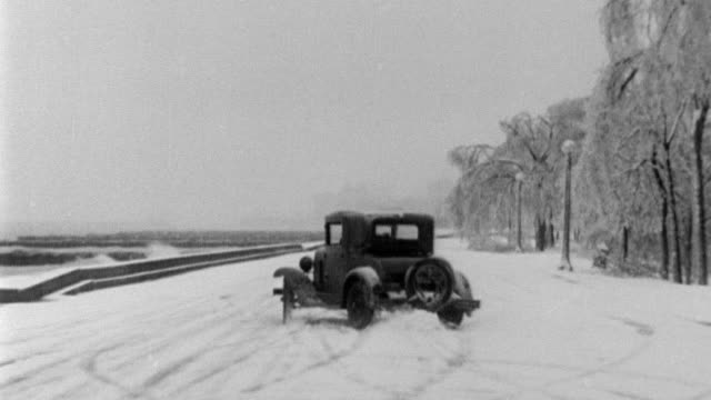 vidéos et rushes de frozen statute of a soldier / trees bent over because of weight of ice / road closure signs / cu ice crusted tree branches / car skids through down... - 1933