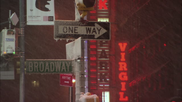 cu frozen street signs in times square at snowy night with neon signs in background / new york city, new york, usa - frozen stock videos and b-roll footage