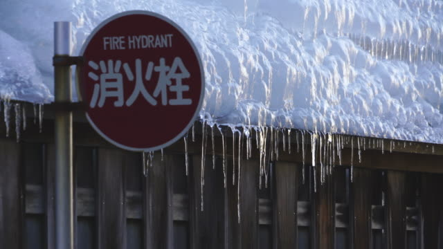 frozen wooden fence of ryokan (traditional japanese inn) behind the fire hydrant sign at shibu onsen (shibu hot spring) yamanouchi-machi, nagano japan on feb. 17 2019. - jigokudani monkey park stock videos & royalty-free footage
