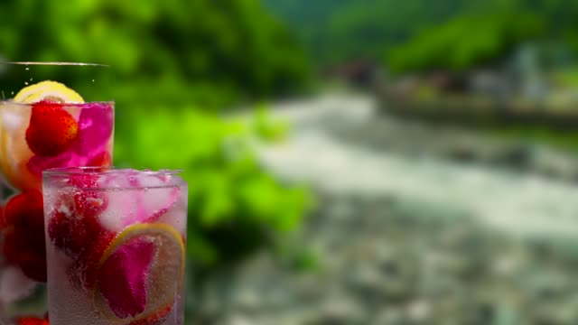 Fruit drinks on the mountain river background