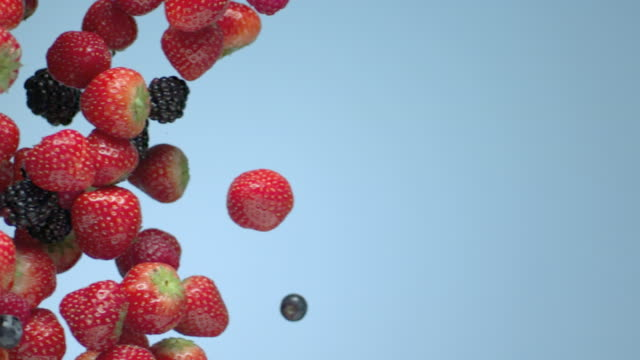 fruit floats over a blue background. - fragola video stock e b–roll