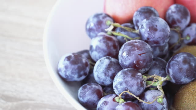 fruit mix with grape, apple, kiwifruit for healthy breakfast on table. - blueberry stock videos and b-roll footage