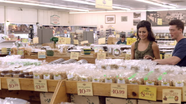ws pan fruit orchard store selling dried fruit and nuts in plastic bags as shoppers browse aisles / cabazon, california, usa - greengrocer's shop stock videos and b-roll footage
