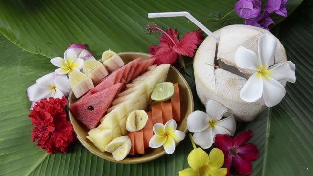 cu fruit salad and coconut drink decorated with frangipani flower / mae nam, ko samui, thailand    - fruit salad stock videos & royalty-free footage