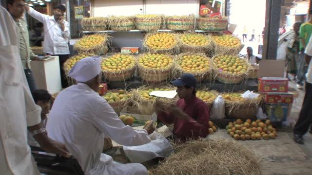 MS ZI Fruit vendor and assistants packing mangoes, Mumbai, India