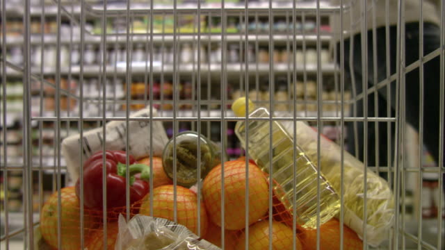 CU POV Fruits and oil bottle in shopping trolley, shoppers walking in background / North Finchley, London, UK