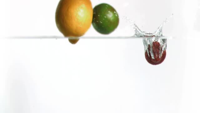 fruits falling into water in super slow motion - gruppe von gegenständen stock-videos und b-roll-filmmaterial
