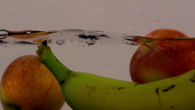 fruits splashing into water (super slow motion) - slip banana stock videos & royalty-free footage
