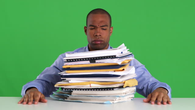 Frustrated and overwhelmed businessman pushing pile of work off desk