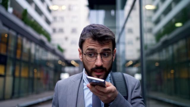 vídeos de stock e filmes b-roll de frustrated businessman leaving a voice message to his coworker to fix a problem at work - one mid adult man only