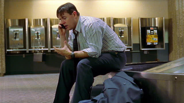 MS PAN frustrated businessman sits on airport baggage claim, talks on cell phone + shakes head