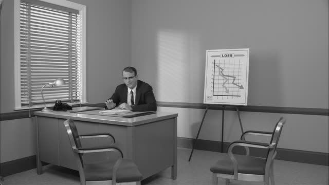 b/w ms frustrated businessman sitting down at desk near graph showing loss/ man breaking pencil/ new york city - broken pencil stock videos & royalty-free footage