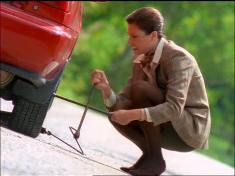 canted frustrated businesswoman changing tire with lug wrench - lug wrench stock videos and b-roll footage