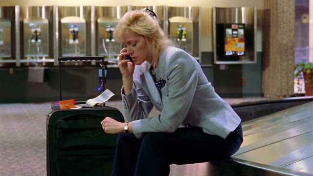 MS frustrated businesswoman sits on airport baggage claim, talks on cell phone + shakes head
