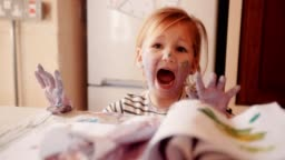 Frustrated child dirty with paints having a tantrum