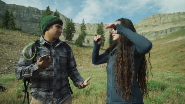frustrated couple on mountain checking for cell phone signal / mount timpanogos, utah, united states - struggle stock videos and b-roll footage