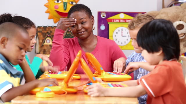MS PAN Frustrated Educator in Daycare, Surrounded by Yelling Children / Richmond, Virginia, USA