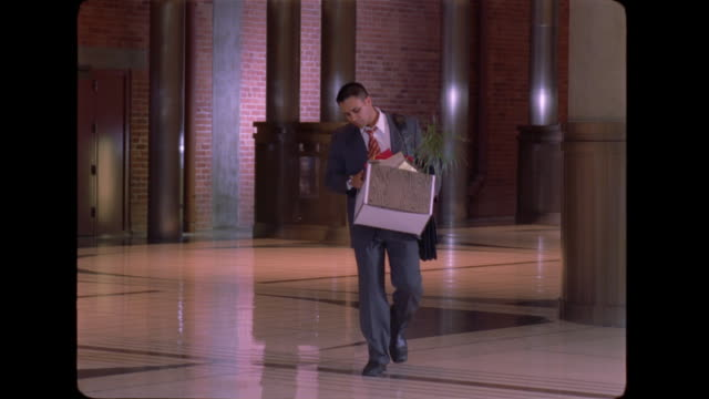 A frustrated  Latino businessman shakes his head while carrying a box of belongings through the lobby of an office building.
