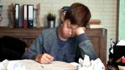 Frustrated little boy tired of his homework crumples his paper