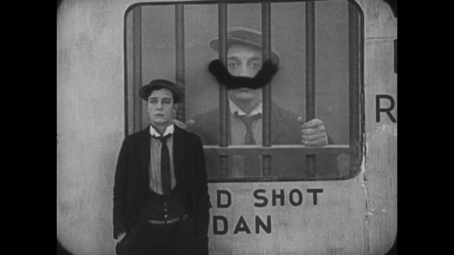 vídeos y material grabado en eventos de stock de 1921 frustrated man (buster keaton) places disguise on wanted poster depicting his face - moustache