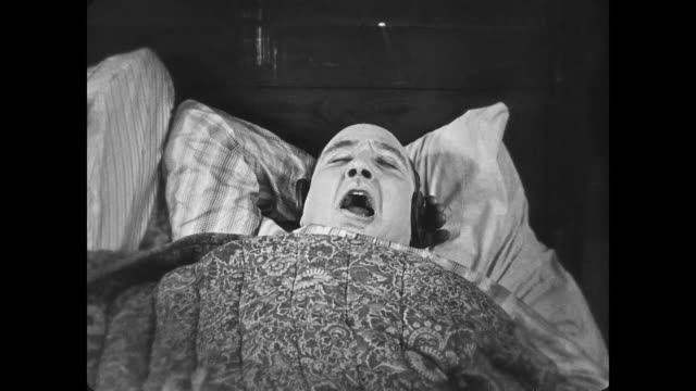 1922 frustrated man steals headphones from snoring bed mate - snoring stock videos and b-roll footage