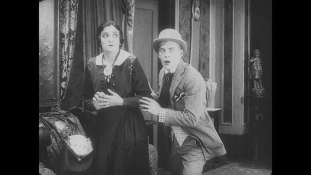 1917 frustrated man (buster keaton) tells woman of her stolen jewelry as an unaware man (fatty arbuckle) visits house of thieves - deception stock videos and b-roll footage