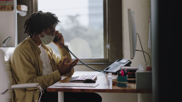 frustrated office worker in face mask using computer picks up phone to have conversation, hangs up phone, leans back in chair with hands covering face - streiten stock-videos und b-roll-filmmaterial