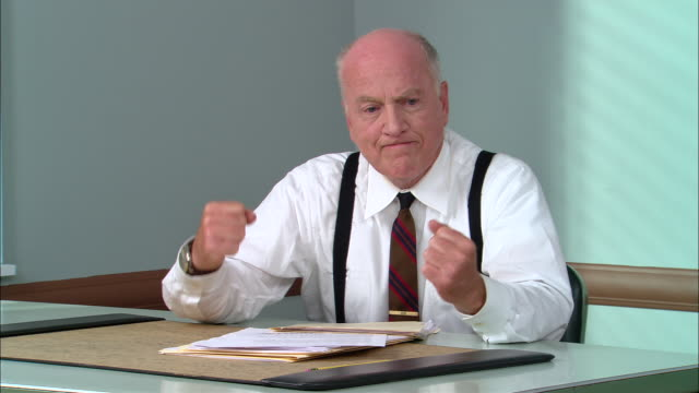 MS Frustrated senior businessman sitting at desk with head in hands/ Man shaking fists and breaking pencil/ New York City