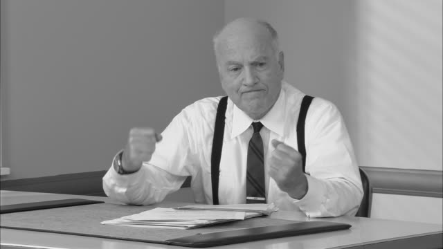b/w ms frustrated senior businessman sitting at desk with head in hands/ man shaking fists and breaking pencil/ new york city - suspenders stock-videos und b-roll-filmmaterial