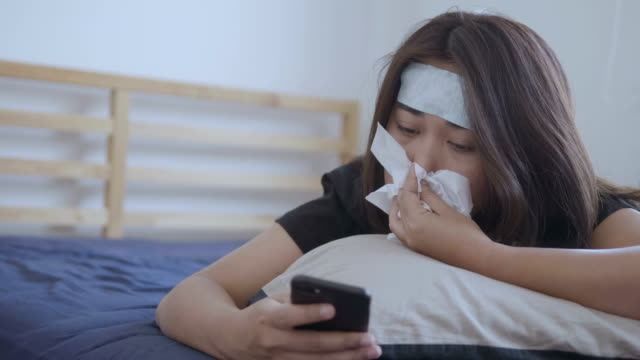 frustrated sick woman lying on a bed and sneezing - infectious disease stock videos & royalty-free footage