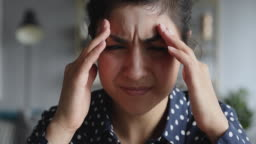 Frustrated stressed young indian woman coping with headache migraine, closeup