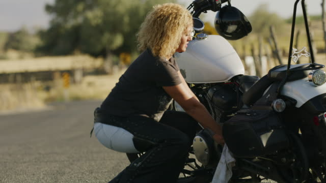 Frustrated uncertain woman on road with broken down motorcycle / Payson, Utah, United States