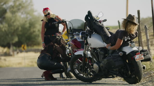 vidéos et rushes de frustrated uncertain women on road with broken down motorcycle / payson, utah, united states - payson
