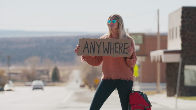 vidéos et rushes de frustrated woman holding anywhere sign hitchhiking on remote rural road / loa, utah, united states - sign