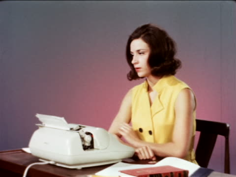 1967 frustrated woman in yellow typing in studio / makes mistake + erases it / industrial - archivmaterial stock-videos und b-roll-filmmaterial