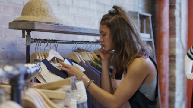 Frustrated woman talking on cell phone in clothing store / Provo, Utah, United States