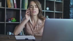 Frustrated woman talking on mobile phone. Business lady working in office