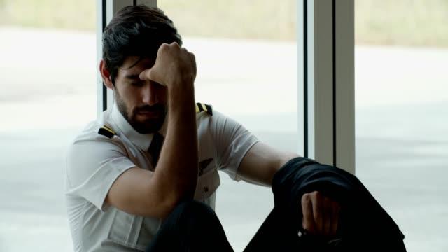 frustrierter junger mann pilot fühlt sich bei der arbeit gestresst - pilot stock-videos und b-roll-filmmaterial