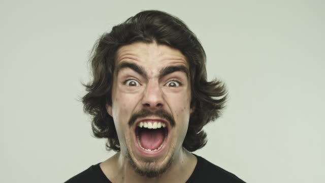 Frustrated young man screaming on gray background