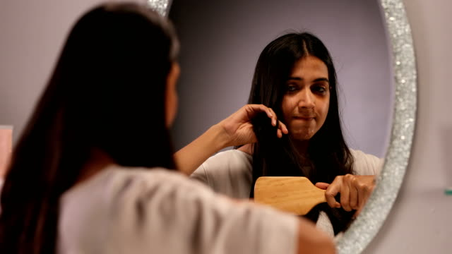 "vídeos y material grabado en eventos de stock de ""cu frustrated young woman brushing her tangled hair with hair brush in front of mirror/ new delhi, delhi, india "" - cepillar el cabello"
