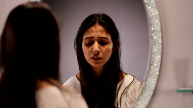 """cu frustrated young woman holding her hair in front of mirror/ new delhi, delhi, india "" - specchio video stock e b–roll"