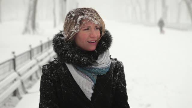 vídeos de stock e filmes b-roll de cu frustrated young woman in park in blizzard / new york city, new york, usa - olhar em redor