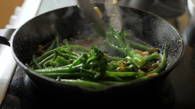 fry off broccoli stem, green beans with sliced garlic and capers on skillet pan - cooking pan stock videos & royalty-free footage