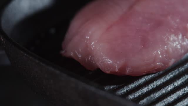 vídeos de stock e filmes b-roll de frying a turkey breast fillet - cortado em filete