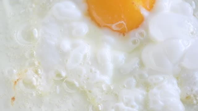 vídeos y material grabado en eventos de stock de frying an egg in vegetable oil, close-up in slow motion - huevos fritos de un solo lado